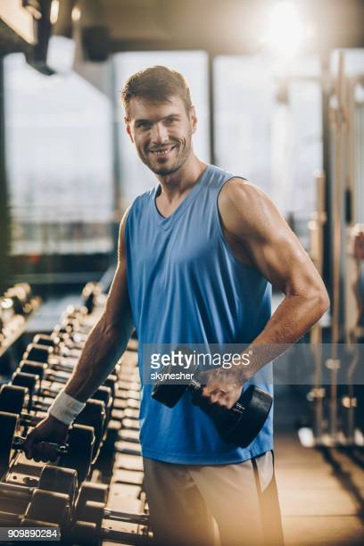 happy athletic man taking weights from the rack in a health club. - only young men stock pictures, royalty-free photos & images