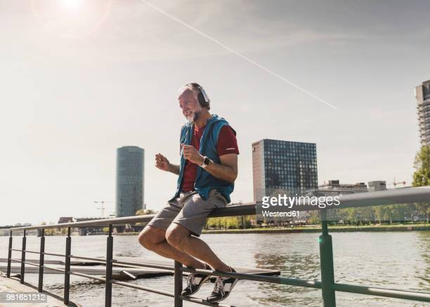 happy athletic mature man with headphones sitting at the riverside in the city - freizeitaktivität stock-fotos und bilder