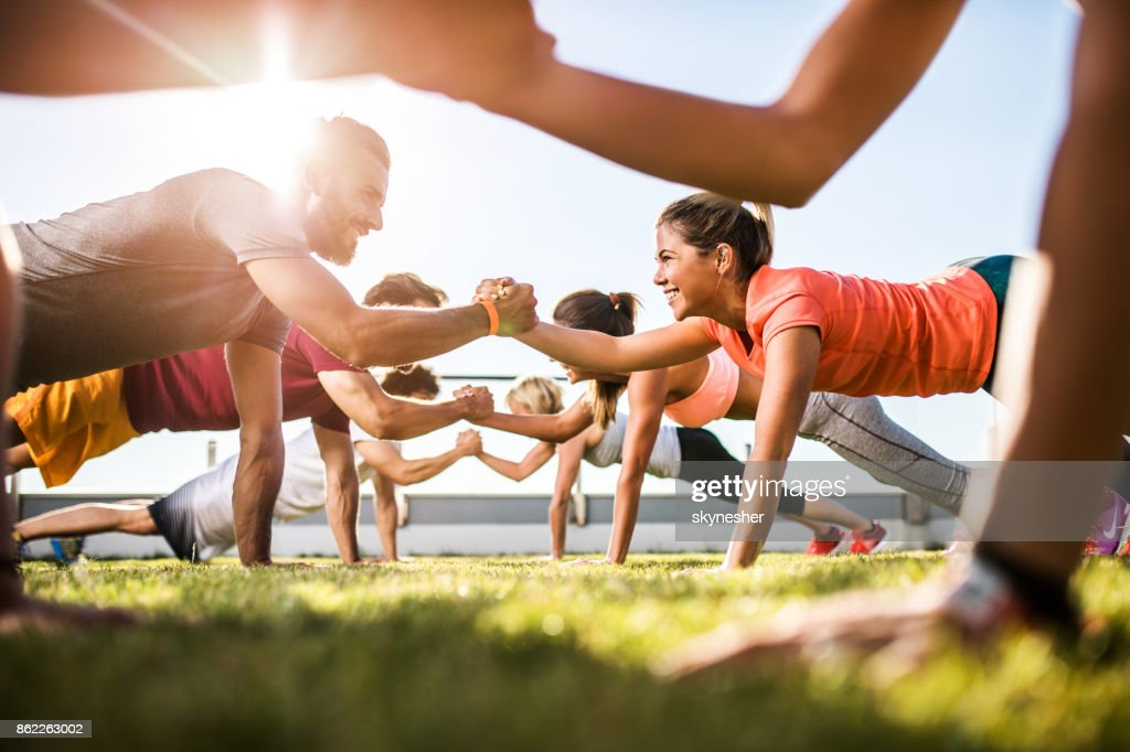 Happy athletic people cooperating while exercising on a sports training. : Stock Photo