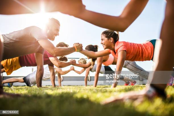 happy athletic people cooperating while exercising on a sports training. - sports training stock pictures, royalty-free photos & images