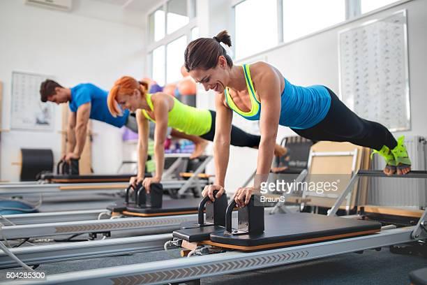 Feliz athletic personas hacen ejercicio en equipos de Pilates en el gimnasio.