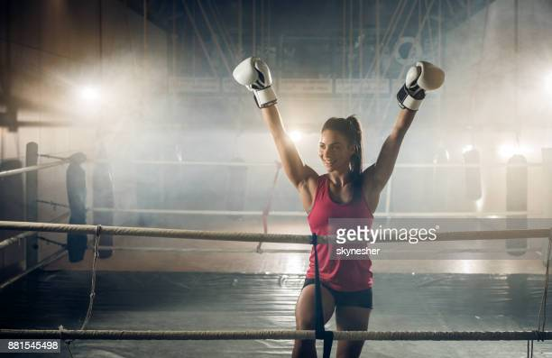 happy athletic woman celebrating victory after boxing match in a ring. - fighting ring stock pictures, royalty-free photos & images