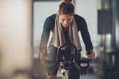 Happy athletic woman cycling on exercise bike in a gym.
