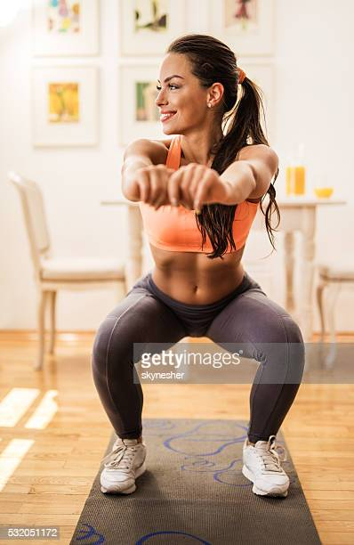 happy athletic woman exercising at home and doing squats. - hurken stockfoto's en -beelden