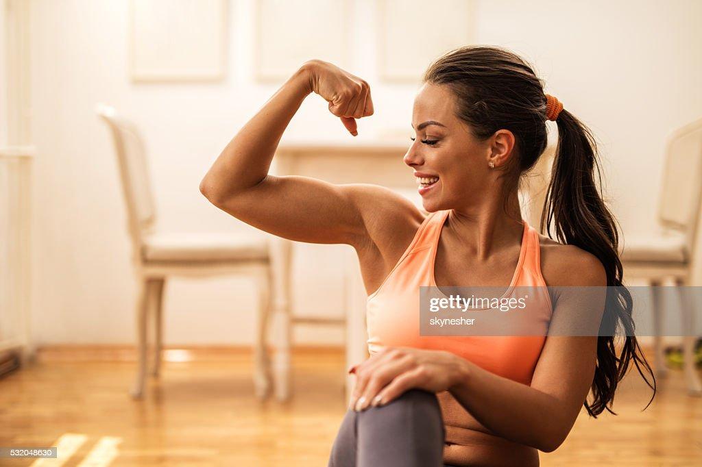 Feliz mujer atlética flexión de bíceps en su hogar. : Foto de stock