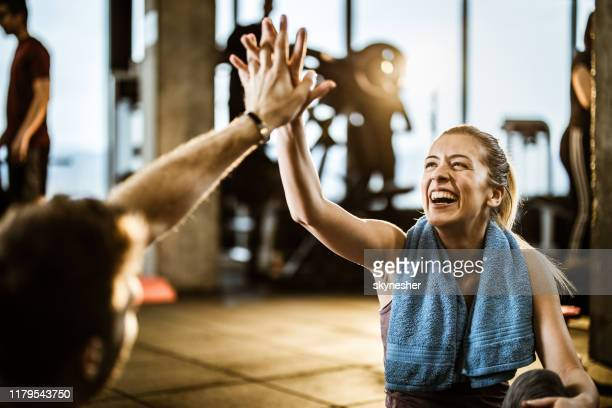 happy athletic woman giving high-five to her friend on a break in a gym. - sports training stock pictures, royalty-free photos & images