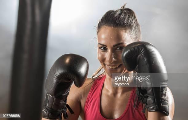 feliz mulher atlética em um boxe luta postura no health club. - combat sport - fotografias e filmes do acervo