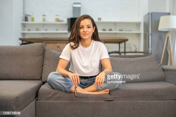 happy attractive lady resting on sofa in living room - white t shirt stock pictures, royalty-free photos & images