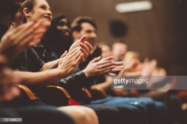 happy audience applauding in the theater - applauding stock pictures, royalty-free photos & images