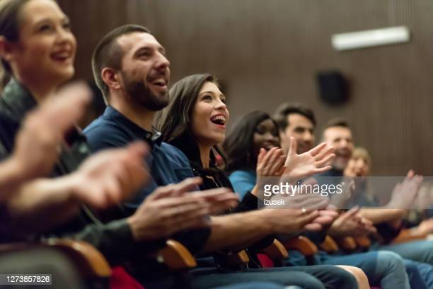 happy audience applauding in the theater - audience stock pictures, royalty-free photos & images