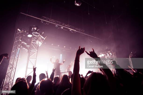 happy audience enjoying rock music concert - rock group stock photos and pictures