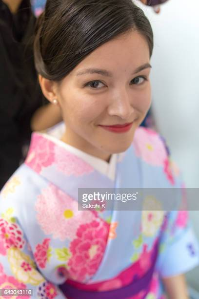 Happy Austrian woman in Kimono making up in fitting room