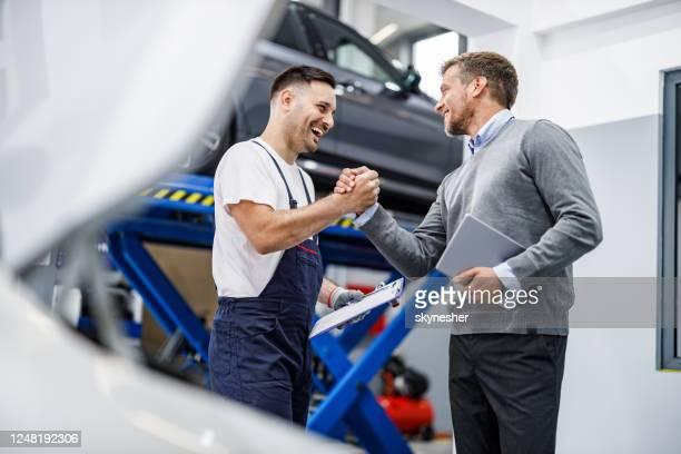 feliz mecânico de automóveis e seu gerente cumprimentando em uma oficina. - cliente - fotografias e filmes do acervo