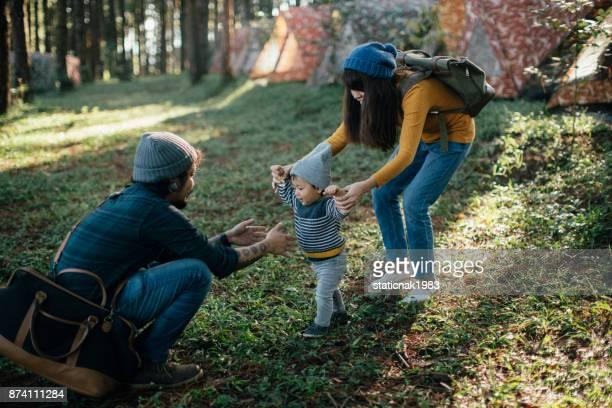 Bebé feliz niño haciendo sus primeros pasos en la hierba en el bosque.