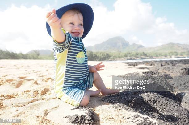 Happy Baby Boy Playing At Beach Against Sky