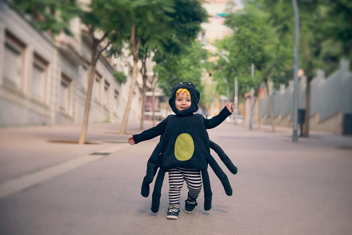 Happy baby boy running dressed as a spider - gettyimageskorea