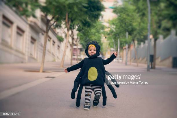 happy baby boy running dressed as a spider - halloween kids stock photos and pictures