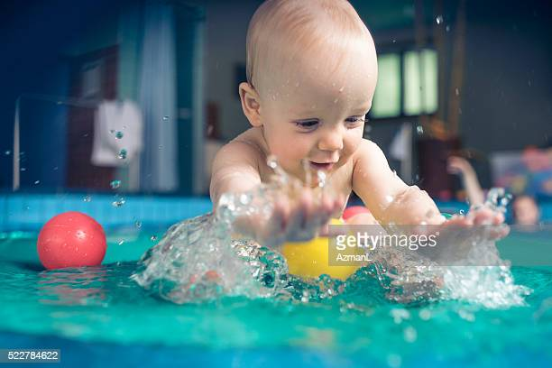 Happy baby boy splashing