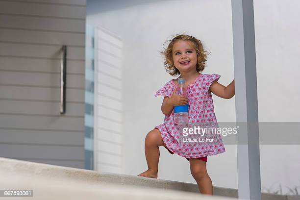Happy baby girl holding a water bottle