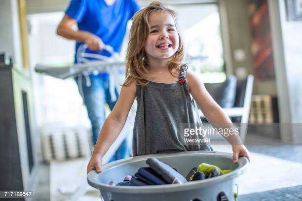 Happy baby girl holding laundry basket
