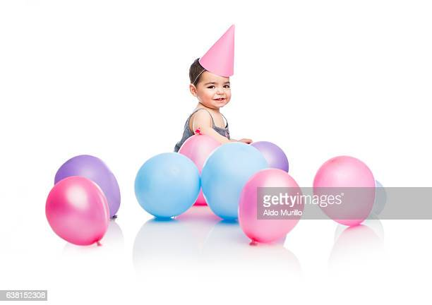 Happy baby girl with party balloons and hat