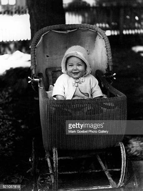Happy baby in buggy, late 1930s.