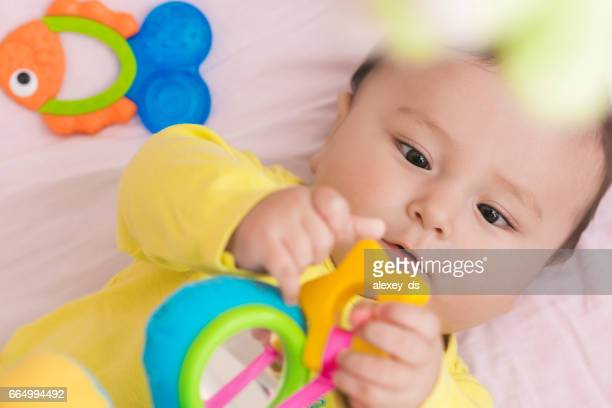 Happy baby lying in his crib looking at toy intently