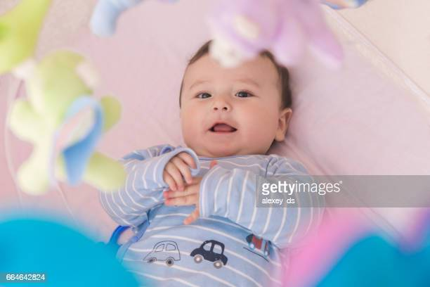 Happy baby lying in his crib smiling