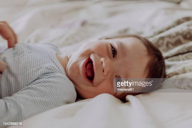 happy baby, lying on bed, laughing - kleinstkind stock-fotos und bilder