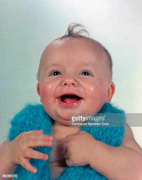 Happy baby wearing blue knitted scarf