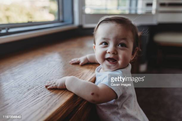 happy baby with first teeth holding herself upright near window - neo foto e immagini stock