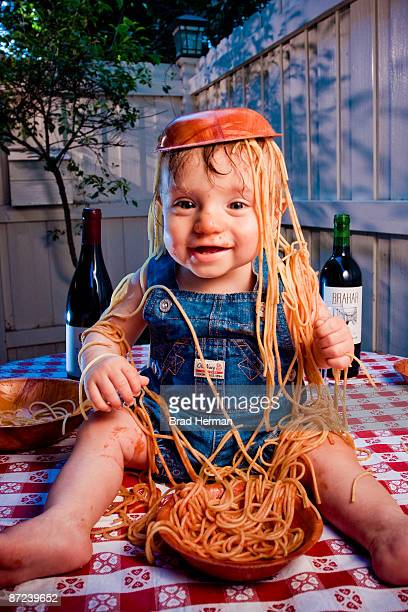 happy baby with spaghetti and bowl on his head - kitchen utensil stock pictures, royalty-free photos & images