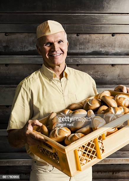 Happy baker carrying crate of bread rolls