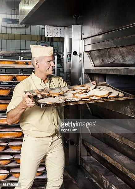 Happy baker placing tray of sliced bread into oven
