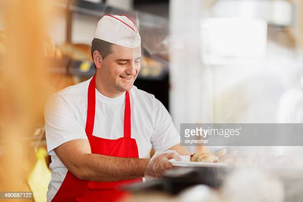 Happy baker working in bakery.