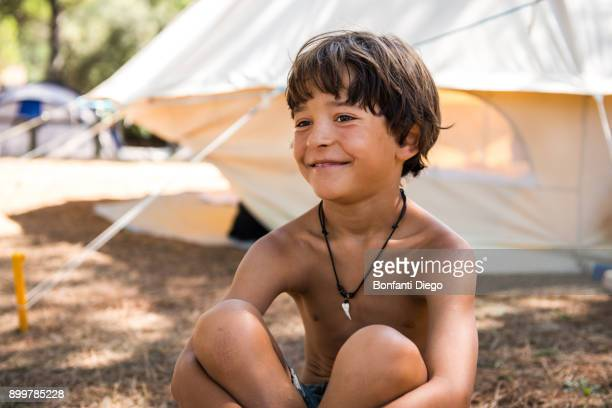 happy bare chested boy sitting on campsite - chest barechested bare chested fotografías e imágenes de stock