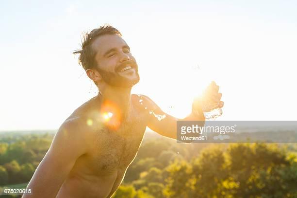 happy barechested athlete pouring water over his body at sunset - ragazzi fighi nudi foto e immagini stock