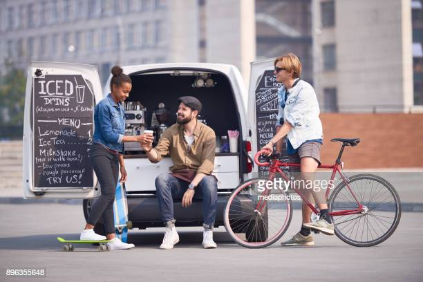Happy barista giving coffee to hipster girl