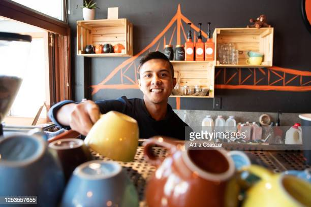 happy barista putting coffee cups to place after reopening - australia stock pictures, royalty-free photos & images