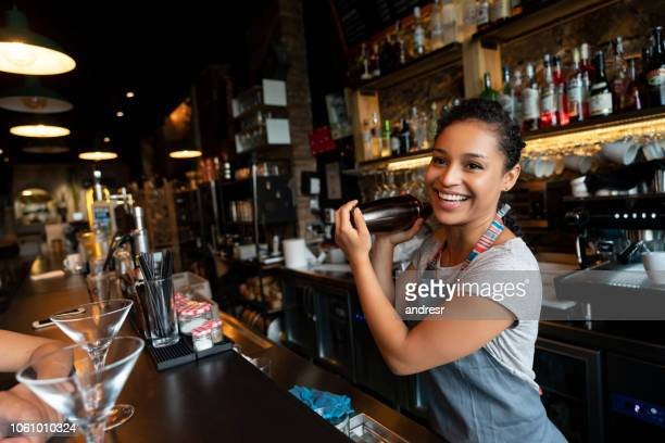 happy bartender mixing drinks at the bar - bartender stock pictures, royalty-free photos & images