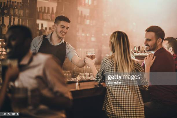 happy bartender serving his customers with beer in a pub. - wait staff stock pictures, royalty-free photos & images