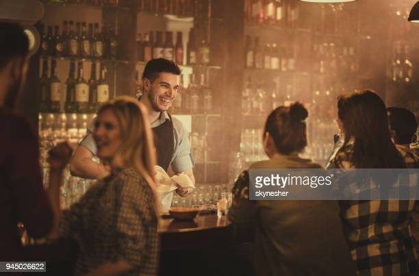 happy bartender talking to his customers in a pub. - pub stock pictures, royalty-free photos & images