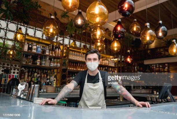 feliz bartender trabalhando em um bar usando uma máscara facial - balcão de bar - fotografias e filmes do acervo