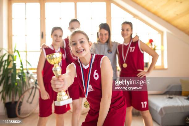 happy basketball player holding trophy and medal in front of team - medallist stock pictures, royalty-free photos & images