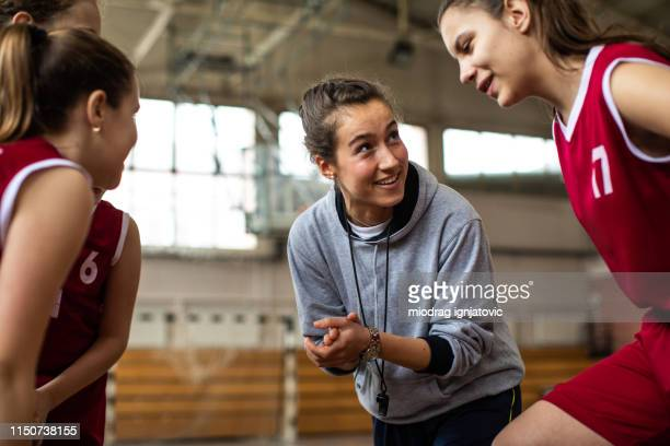 happy basketball team with their cheerful female coach - physical education stock pictures, royalty-free photos & images