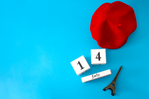 Happy Bastille day and French national day concept with a flat lay image of red beret, a block calendar set on July 14, a miniature of the Eiffel Tower isolated on blue background with copyspace 1135762202