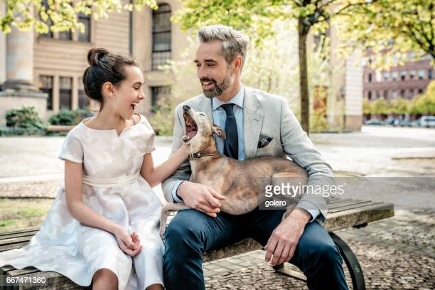 happy bearded father on bench with festive dressed daughter and dog