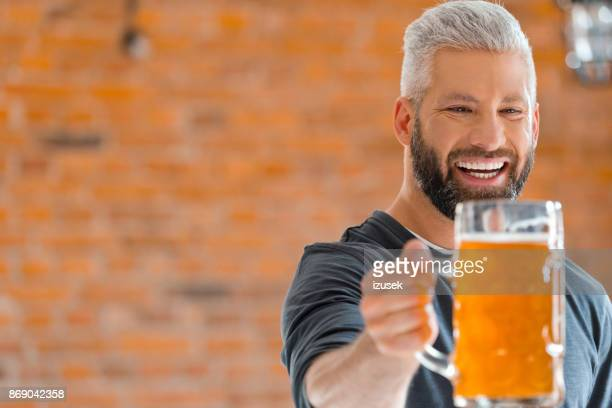 happy bearded man holding mug of beer in pub - microbrewery stock photos and pictures