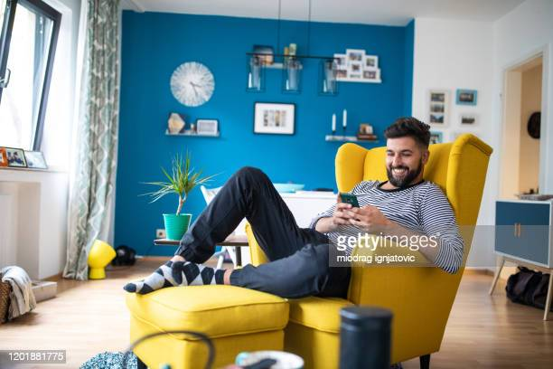 happy bearded man sitting on armchair and using smart phone - one man only stock pictures, royalty-free photos & images