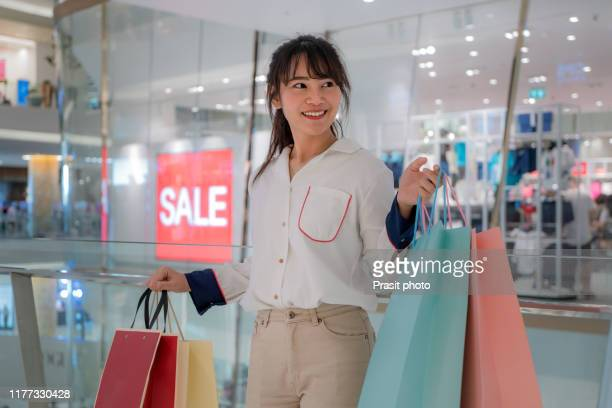 happy beautiful asian woman smile and hold shopping bags with sale sign, copy space on shopping mall background. shopaholic people, rich girl spending money lifestyle, or department store payment concept - rich's_(department_store) stock pictures, royalty-free photos & images